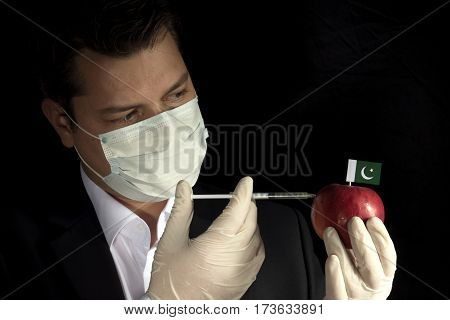 Young Businessman Injecting Chemicals Into An Apple With Pakistani Flag On Black Background
