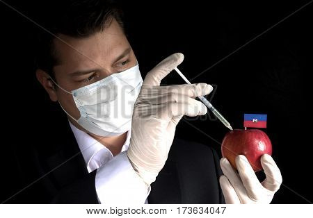 Young Businessman Injecting Chemicals Into An Apple With Haitian Flag On Black Background