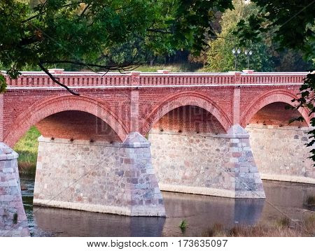 beautiful small bridge made of red and white stone in the form of large arches, around trees, shrubs and other vegetation, green leaves, summer,
