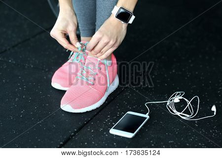 Young woman with fitness tracker and mobile phone tying shoelaces in gym