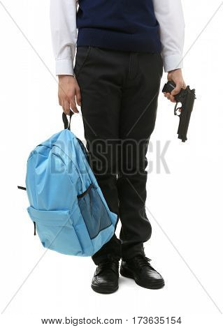 Schoolboy holding backpack and gun on white background