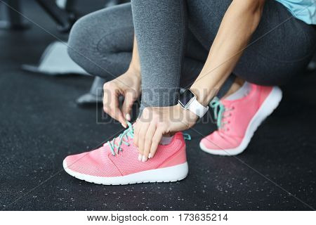 Young woman with fitness tracker tying shoelaces in gym, closeup