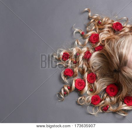 Beautiful young woman with flowers in hair on gray background
