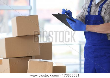 Male courier with clipboard on boxes background