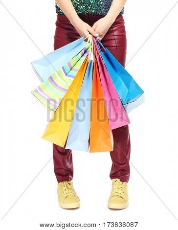 Woman's legs and shopping bags on light background