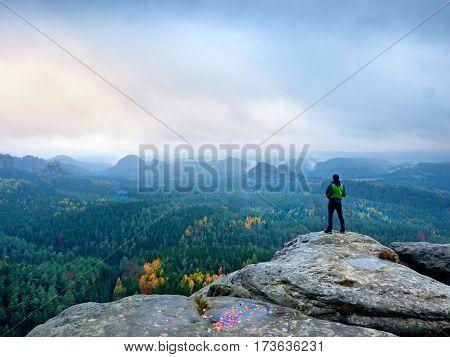 Hiker In Green Windcheater, Cap And Dark Trekking Trousers Stand On Mountain Peak Rock.