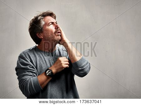Anxious unhappy mature man portrait over gray background