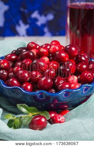 Red cranberry juice in a glass cranberries in the blue clay bowl on the table blue wall