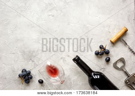 glass bottle of red wine with fresh grapes on stone texture background top view mock-up