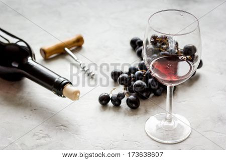 Glass of red wine, grape and bottle on white stone background