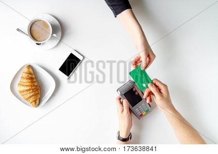 business lunch with cup of coffee and croissant credit card payment in cafe on white table background top view