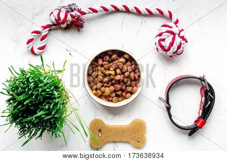 dry dog food in bowl on stone background top view.