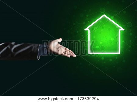 Male hand pointing to the glowing home icon or symbol