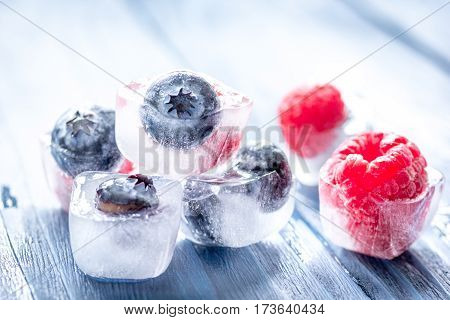 Frozen fresh berry in ice cubes on blue wooden table background
