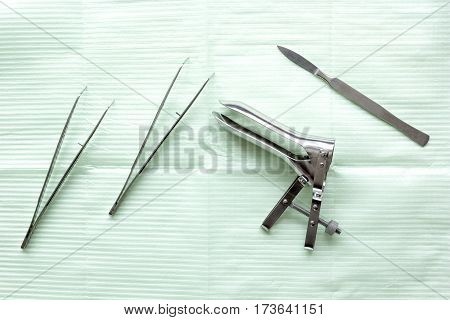 instruments of gynecologist on green background top view.