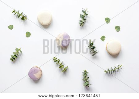 Trendy spring design in pastel color with macaroons and flowers on white background top view