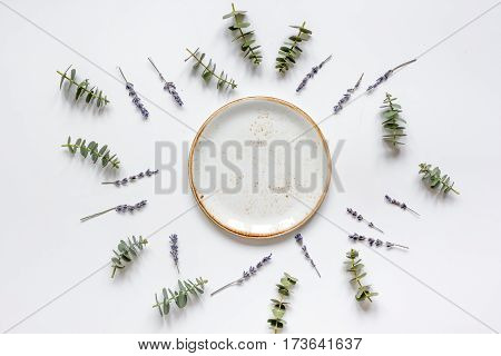 Trendy design in pastel color with plate, eucalyptus and lavander on white background top view mock up
