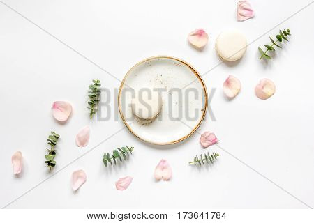 flat lay in pastel colors with rose petals and macaroons on white table background top view
