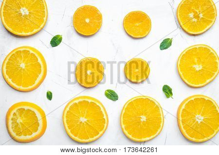 Fresh orange slices with mint leaves on white table background top view pattern