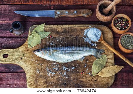 Fresh fish smelt for cooking on a kitchen board near spices in wooden jars