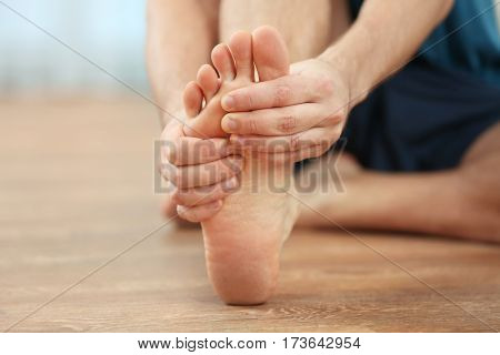 Young man suffering from podalgia at home, closeup