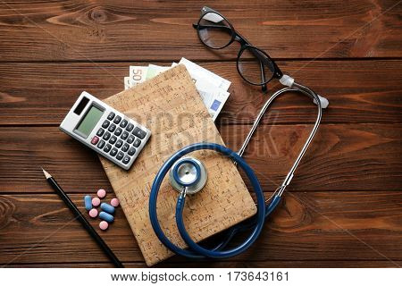 Medical concept. Notebook with money, calculator, stethoscope and pills on wooden table, top view
