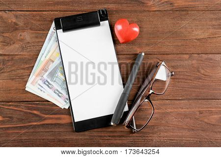 Clipboard with money on wooden background. Medical concept
