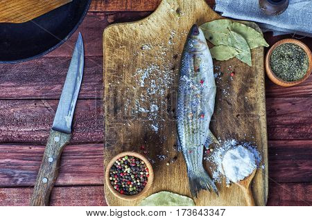 Fresh fish smelt for cooking lies next to a knife with a frying pan