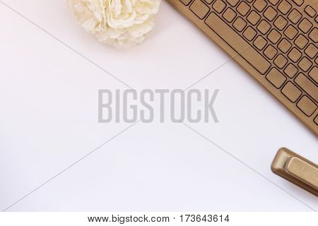 Chic minimalist design of a white and gold desktop with flowers, keyboard and stapler. Room for copy.
