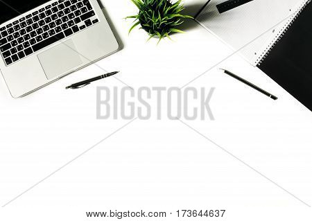 White office desk frame with laptop keyboard and supplies. Laptop, notebook, pen, clips, pencil, plant and office supplies on white background. Flat lay, top view, mockup