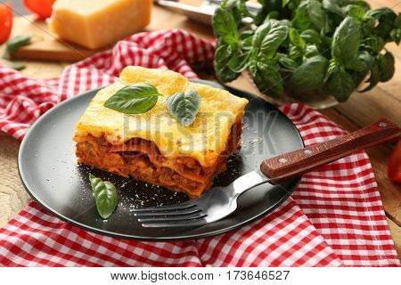 Black plate with delicious lasagna and red napkin on table