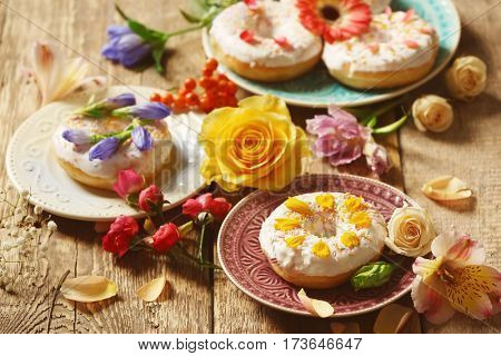 Composition of plates with delicious donuts and colourful flowers on wooden table, closeup