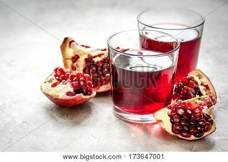 ripe pomergranate and glass of fresh juice on stone table background