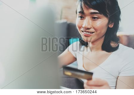 Happy young Asian woman using laptop and golden creditcard for online shopping at home.Blurred background, flares effect