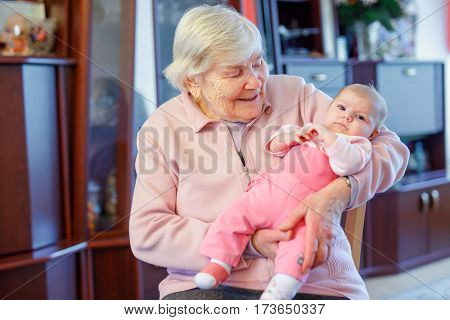 Great grandmother holding newborn baby grandchild on arm. Happy senior woman with cute little baby daughter.