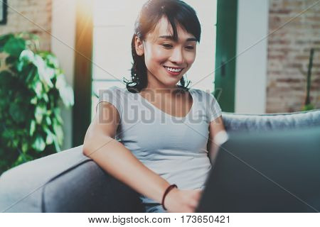 Portrait of attractive young Asian woman sitting at sofa and working modern laptop at home, wearing white tshirt.Horizontal, blurred backgroung, flare effect