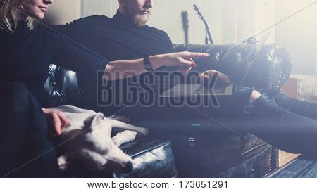 Bearded coworker working at the home.Man sitting in vintage sofa, using contemporary notebook.Woman pointing hand to laptop screen.Horizontal, visual effects