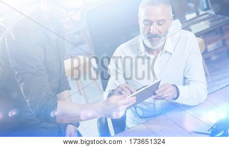 Group of two colleagues making great time brake during work process in modern office.Adult bearded man watching digital tablet and smiling.Business people meeting concept.Visual effects