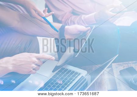 Closeup view of two hands pointing on digital tablet.Group of young coworkers making great business decisions.Blurred background, visual effect. Horizontal.
