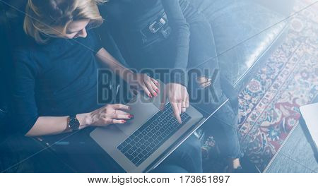 Top view of two young girls working on computer and using mobile devices.Woman wearing black pullover and sitting on the sofa.Horizontal wide, visual effects.Crop