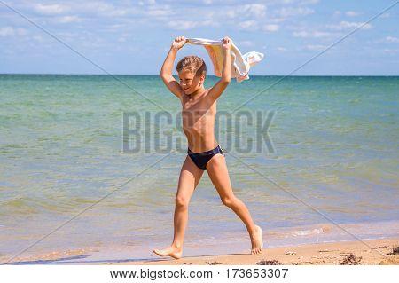 Adorable boy running on coastline with towel