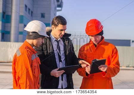 boss or Chief instructs young team of young engineers with a construction project on tablet. They wear overalls and safety helmets. Business modern background