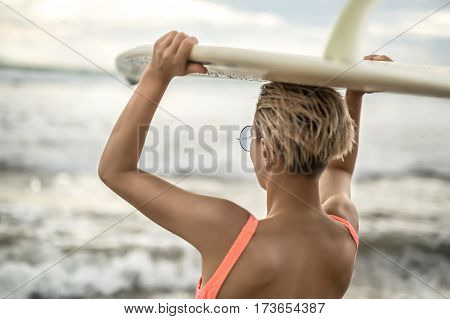 Charming blonde girl with short hairstyle stands backsides on the beach on the background of the sea and cloudy sky. She wears orange swimsuit with sunglasses and holds the surfboard on the head.