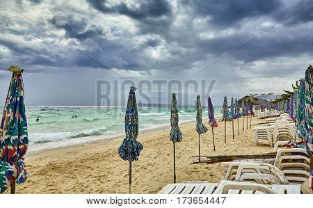 Sun umbrellas and chaise longues folded before the storm Thailand