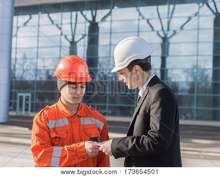 boss or Chief giving salary in an envelope to worker. Good job. Business modern background.