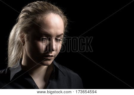 sad young depressed woman on black background