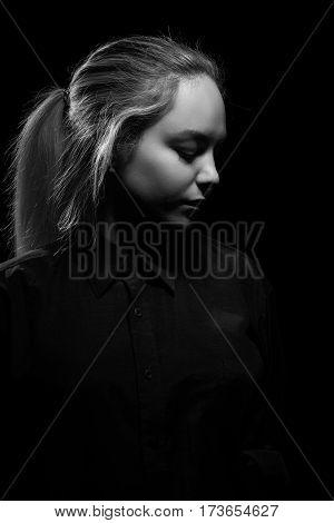 sad woman profile on black background, monochrome