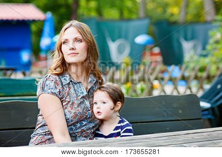 Young mother relaxing together with her little child, adorable toddler girl, in summer outdoors cafe waiting for coffe. Happy family hugging, beautiful woman and tiny cute kid.