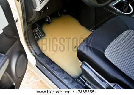 beige car got stuck in a huge pit full of dirty water on a forest road, inside the car a large pool,
