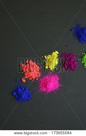 Variety of assorted bright powder colors on dark background.